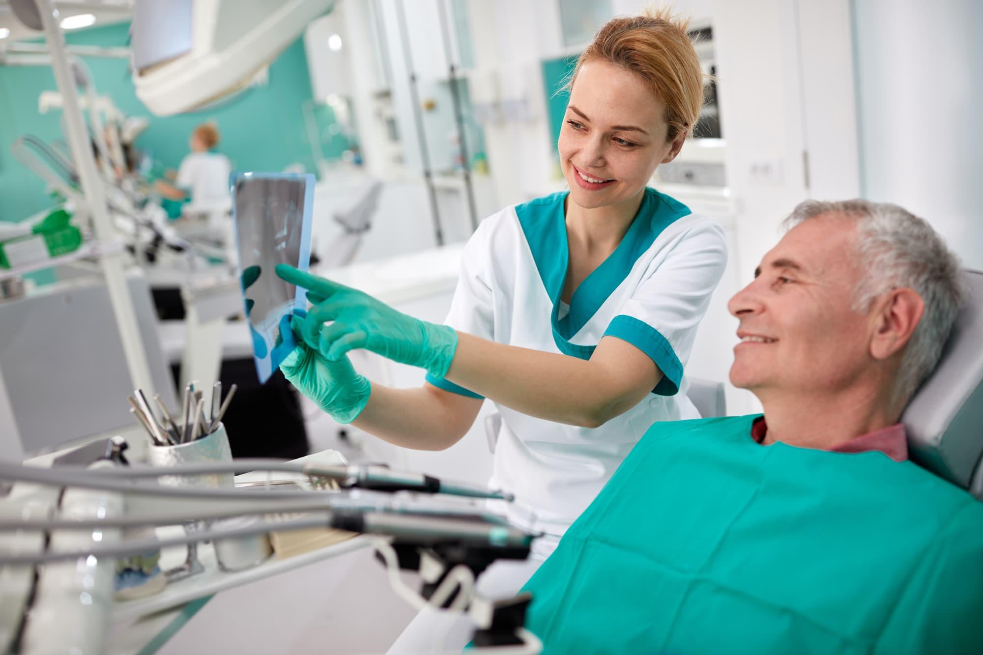 Dentist performing procedure on senior man