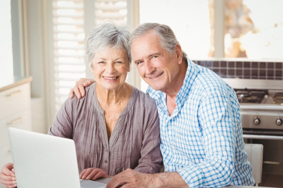 Happy senior couple using a laptop - Medigap Policies