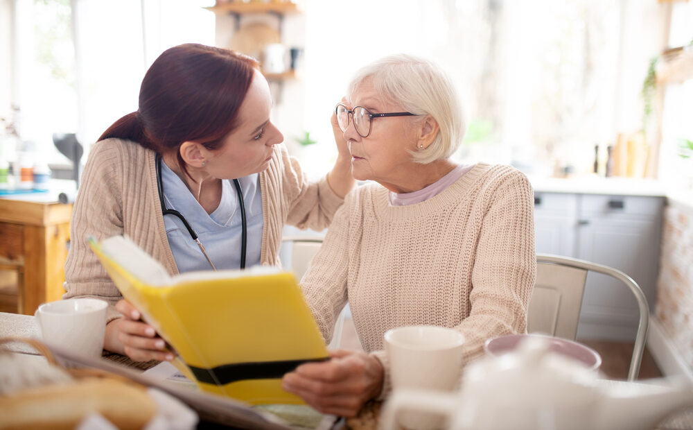 Caring red-haired nurse wearing uniform fixing glasses for retired woman